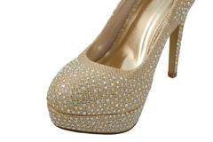 Sparkly toe of a gold fashionable high-heeled shoe Stock Photos