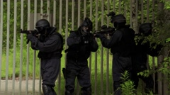 A Special Force squad walk over a street while a car with FBI Agents stop. Stock Footage