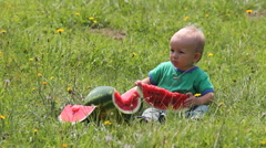 Sweet baby child with a watermelon slice, blond hair dancing in the spring wind Stock Footage