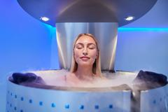Young woman in a whole body cryotherapy cabin Stock Photos