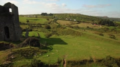 Aerial daytime close up side flyby of derilict Tin Mine on moorland shot Stock Footage