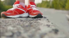 Runner tying shoelaces on the concrete fence, close-up Stock Footage