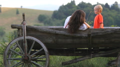 Little boy smiling in a wooden cart, mother relax together with the son Stock Footage