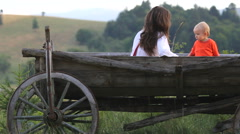 Mother and son in wooden cart resting together Stock Footage
