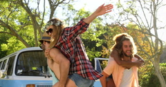 Hipster boys carrying girls on their shoulders Stock Footage