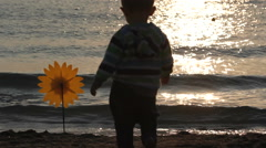 Baby child walking on seashore trying to take hand mill, upset child, waving sea Stock Footage