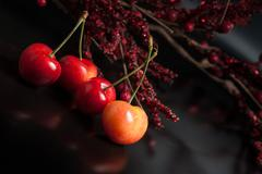 Yellow cherry on black reflective background - stock photo