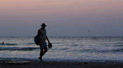 Shoes less man with hat waking on seashore, sunset time Stock Footage
