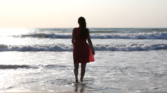 Attractive woman playing, running back and fort to sea waves, wind in long hair - stock footage