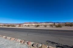 Straight road side with blue sky in Death Valley National Park Stock Photos