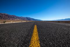 Endless straight road in Death Valley National Park - stock photo