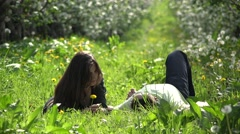 Romantic lovers couple laing on green grass in flourish orchard, pure feelings Stock Footage