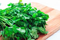 Bunch of fresh coriander on a wooden board Stock Photos