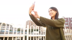 Woman taking selfie by mobile phone at outdoor Stock Footage