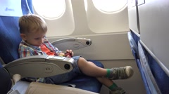 Little child playing with cars toy in the airplane, easy flight Stock Footage