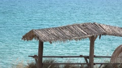 Terrace straw sunshade on beach, blue sea in background Stock Footage