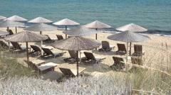 Straw umbrellas, lounge sunbeds, sandy beach and blue sea Stock Footage