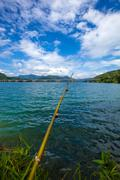 Fishing rod made of tree branch at a tropical lake and islands in cloudy blue - stock photo