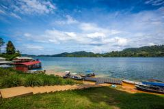 Fishing village of a tropical lake in cloudy blue sky. Belum resort, Banding, - stock photo