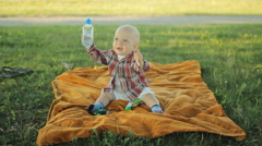 Cute little boy sitting on a blanket in the park. Baby less than a year and he - stock footage