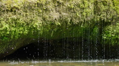 Slow motion spring water dribbling into river, 4K Stock Footage