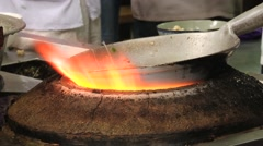 Men prepare Chinese food on fire at a street market in Xian, China. - stock footage