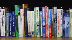 Collection of travel guides about worlwide holiday destinations on bookshelf - stock footage