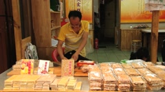Man packs sweets at the stall at a street food market in Xian, China. Arkistovideo