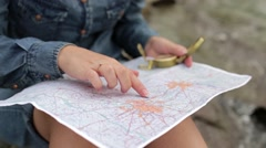 Traveler young woman searching direction with a compass on background of map in Stock Footage