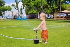 Child play, swim and splash under water sprinkler spray Kuvituskuvat