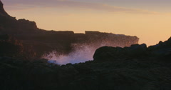 Waves crashing rocky shoreline as sun is setting on piha beach, auckland, New Stock Footage