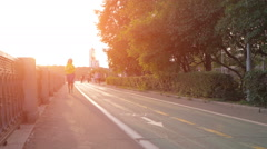 female runner running at sunset in city park - stock footage