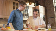 4K Professional chef demonstrating to man how to prepare fresh healthy meal Stock Footage