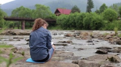 Young woman draws on an easel against the river and the forest background Stock Footage