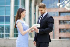 Businesswoman giving a lot of dollars to surprised smiling business men - stock photo