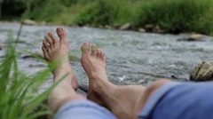 Bare feet tourists vacationing near the river Stock Footage