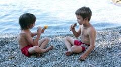 Two happy children, boy brothers, eating ice cream on the beach Stock Footage