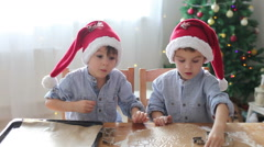 Two cute boys with santa hat, preparing cookies at home, Christmas tree behin - stock footage