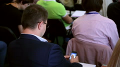 Handsome business man using smartphone on business training seminar - stock footage