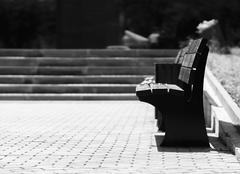 Horizontal black and white right aligned empty bench bokeh backg - stock photo