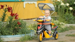Little cute boy sitting in a stroller bike and smiles near the country house - stock footage