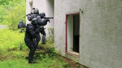 Four Special Force Soldiers run in front of a bedraggled building. Stock Footage