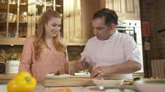 4K Professional chef demonstrating to woman how to prepare fresh healthy meal Stock Footage