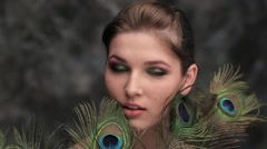 Girl with colored makeup and peacock feather Stock Footage