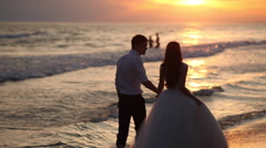 Just married couple walk hand in hand on the beach Stock Footage