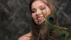 model girl peacock feathers and a beautiful smile - stock footage