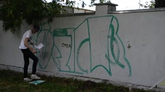 Process of creation of graffiti, fence. - stock footage