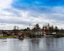 Horizontal dramatic houses on Karelian river bank  background ba Stock Photos