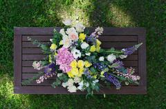 Beautiful flower bouquet outdoors at wooden table top view - stock photo