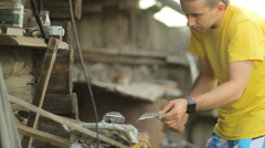 Young man squeezes a metal part in a vise. Against the backdrop of a country Stock Footage